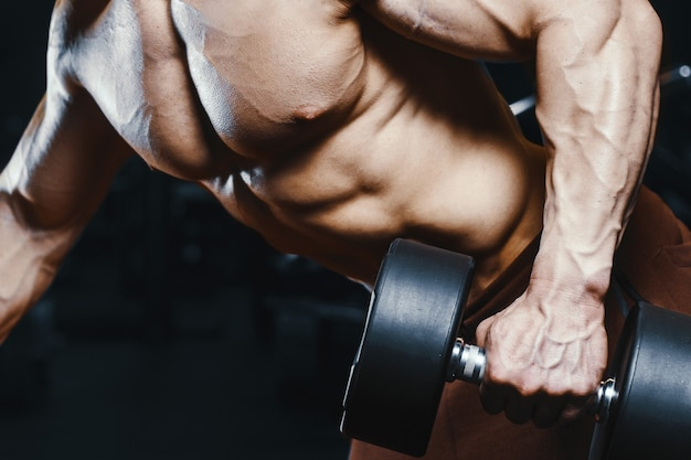 ハンサムな強い運動男性の筋肉トレーニングボディービルをポンプします。