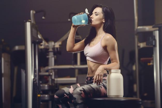 美しい運動若い女性は、ジムで水を飲む