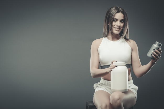 サプリホエイプロテインシェイクパウダーを持つ少女