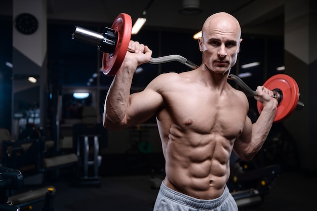 ダンベルで筋肉をポンピングする残忍な強力なボディービルダー運動男性