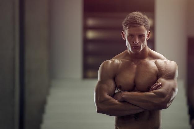 筋肉をポンピングボディービルダーハンサムな強い運動ラフ男