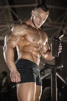 トレーニングの後のフィットネス男飲料水