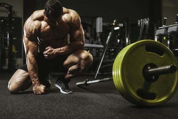 筋肉トレーニングボディービル概念を汲み上げるハンサムな強い運動男性