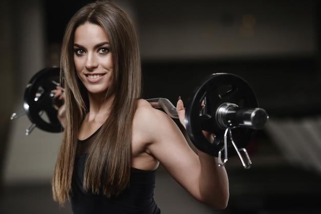 Сильная спортивная молодая девушка, тренируясь в тренажерном зале