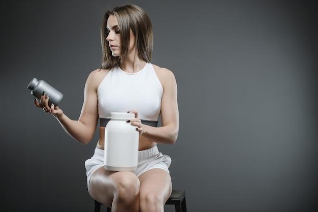 サプリメントホエイプロテインシェークパウダーを持つ少女