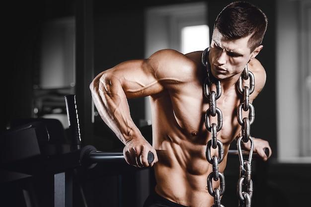 胸の筋肉の腕立て伏せバーを汲み上げるボディービルダー