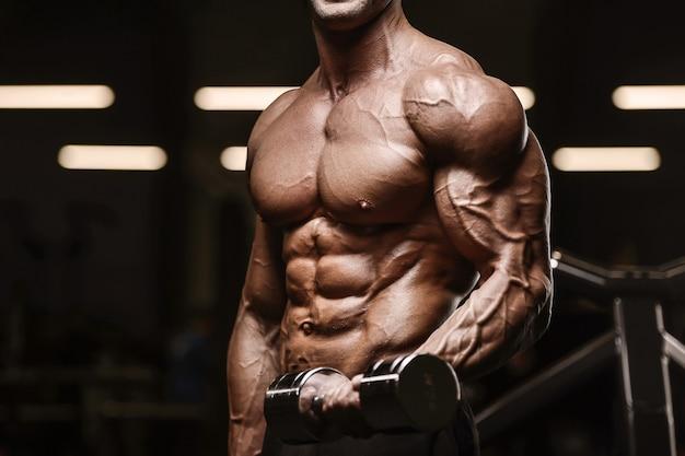 上腕二頭筋の筋肉トレーニングトレーニングとボディービルのコンセプト-ジムの裸の胴体で腕の運動をしている筋肉ボディービルダーフィットネスの男性をポンプでハンサムな強い運動男
