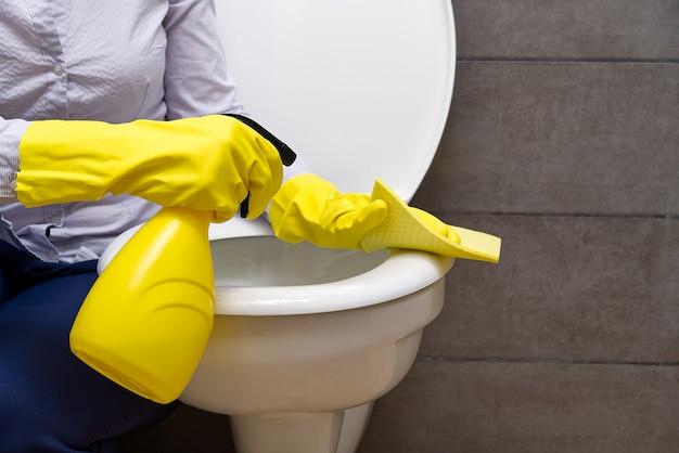 Женщина, уборка туалета. домохозяйка, чистящая туалет или туалет, чистит туалет