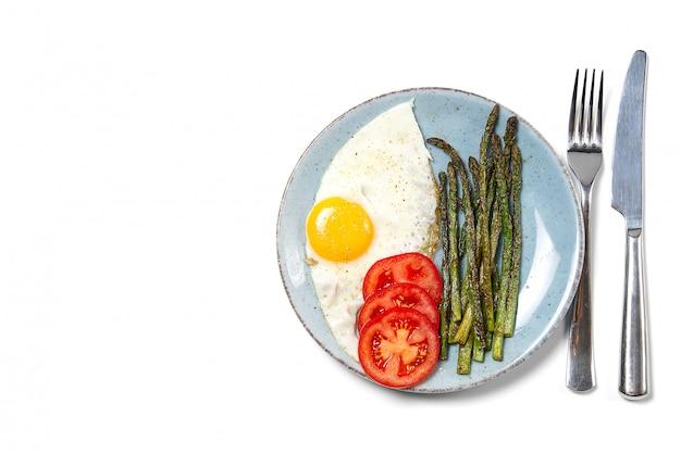 Здоровый домашний завтрак со спаржей, жареными яйцами и рукколой, кето диета.