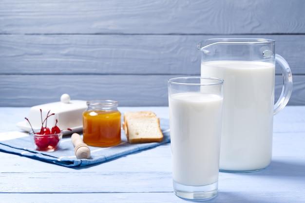 水差しと繁殖と青い木製の背景に牛乳のガラス。