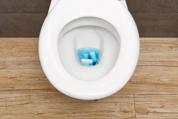 Крупный план туалета, забитого гигиеническими средствами и туалетной бумагой.