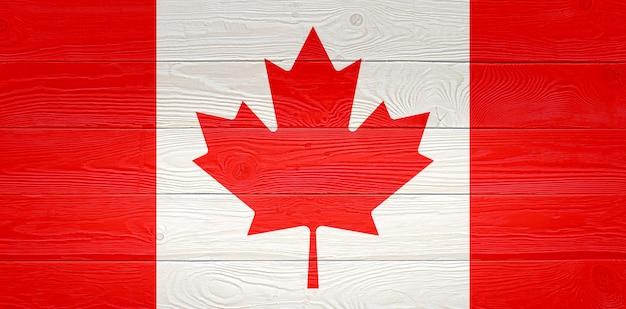 古い木の板の背景に描かれたカナダの国旗