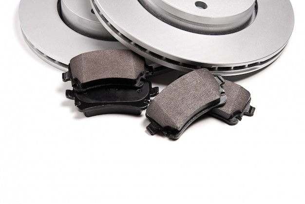 Совершенно новые тормозные диски и комплект тормозных колодок для автомобиля. изолированные на белом с копией пространства.