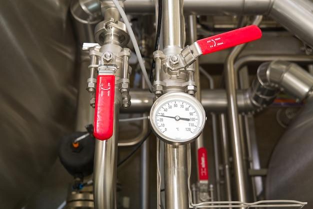 飲料製造用の工場および工業生産プラントでの水の逆流を防止する赤いバタフライゲートバルブ。