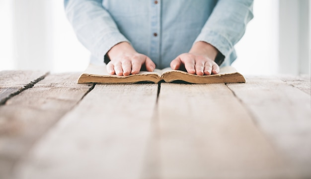 木製のテーブルの上の聖書と祈りの手