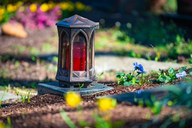 Красная свеча на надгробиях с цветами