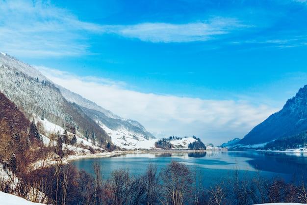 Красивое зимнее озеро и снежные горы. зимний пейзаж