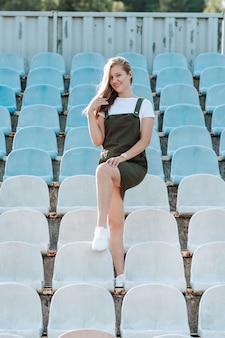 カーキ色のサンドレスを着た少女がスタジアムの席の間に立つ