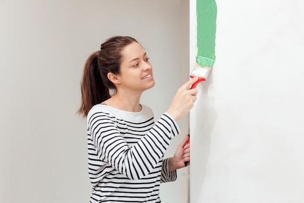 Молодая женщина красит внутреннюю стену кистью