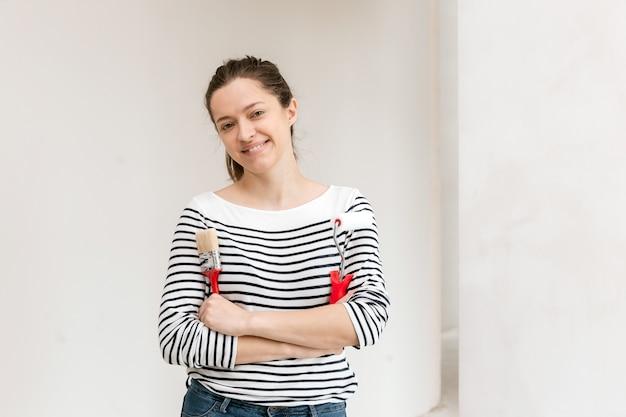 Молодая женщина красит стену валиком и кистью
