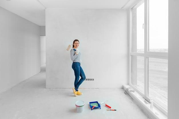 Молодая женщина красит стену валиком