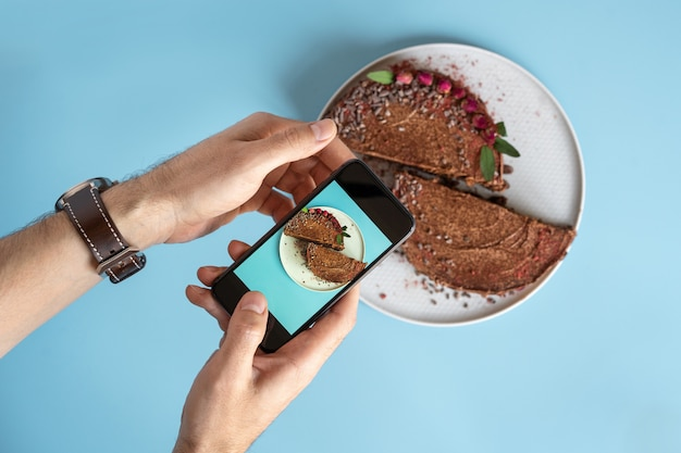男性の手は、青色の背景にスマートフォンでチョコレートケーキの写真を作成します。ブログと食べ物の写真。