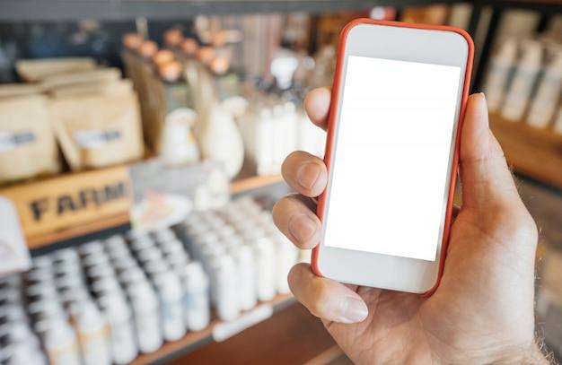 店の棚で携帯電話を持っている男の手、男は製品を購入するか、モバイルアプリケーションで選択します。