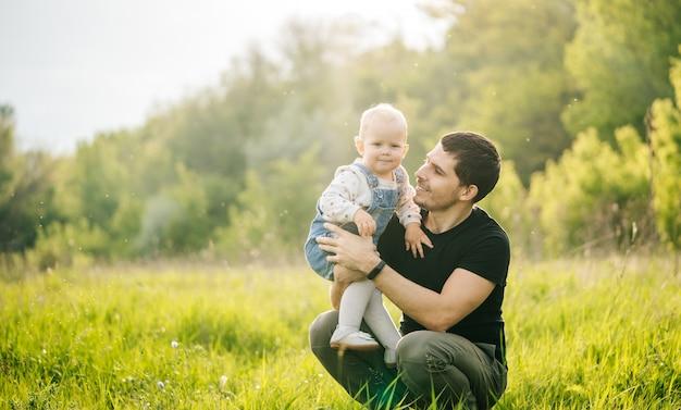 День отца. мужчина гуляет с дочерью в зеленом парке или лесу в теплых лучах солнца.