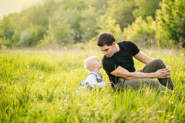 День отца. мужчина и его дочь наслаждаются отдыхом в зеленом парке или лесу в теплых лучах солнца, испытывая семейную радость.