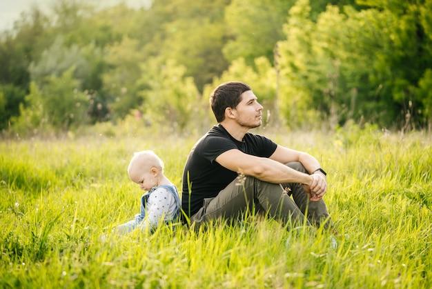 День отца. мужчина и его дочь наслаждаются отдыхом в зеленом парке вечером на закате летом, сидя спиной к спине в траве на лугу.