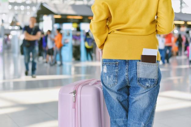 空港ターミナルで荷物を持って立っている旅行者