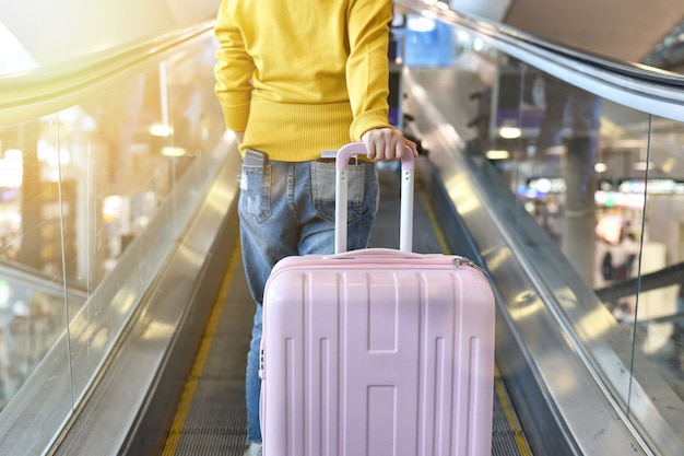 Путешественник несет большой чемодан на эскалаторной дорожке у терминала аэропорта