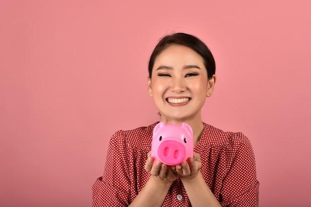 Сбережения денег, азиатская женщина усмехаясь и держа розовую копилку, страхование богатства и финансового планирования для вклада.