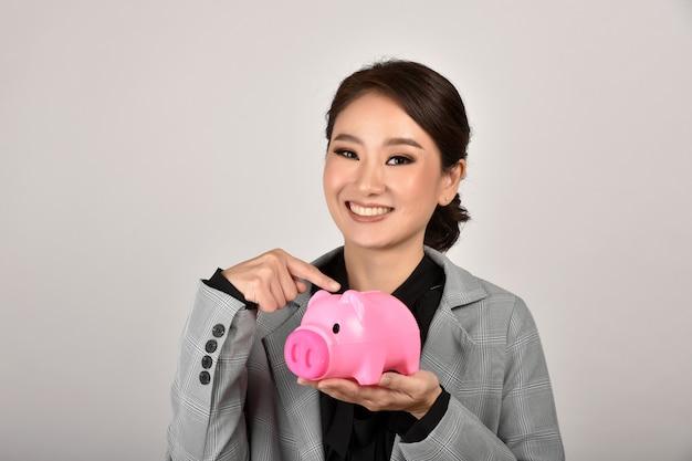 Эксперт по экономии денег финансового советника, азиатская бизнес-леди усмехаясь и держа розовую копилку, страхование богатства и финансового планирования для вклада.