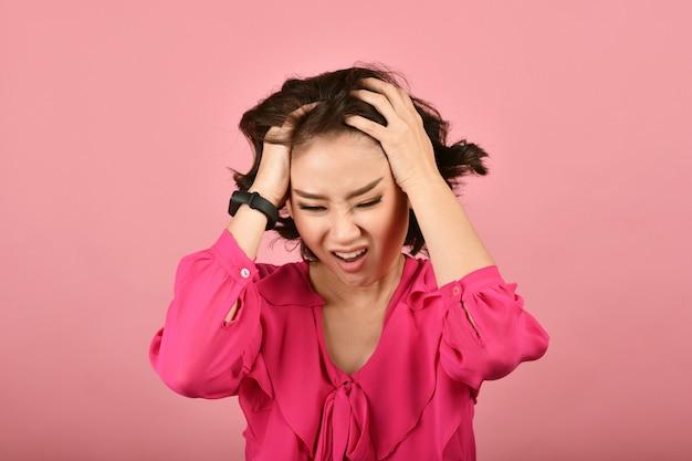 Сердитая азиатская женщина, кричащая женщина с злющим агрессивным жестом на розовой стене, выражение лица и человеческие эмоции.