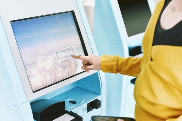 Путешественник с помощью киоска самообслуживания в аэропорту