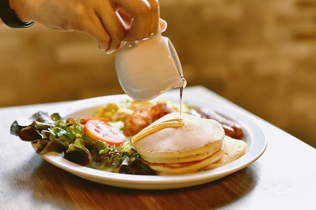 Домашний легкий завтрак, стек блины с сиропом ручной заливки, салат и яичница-болтунья.