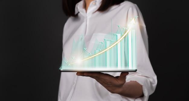 コンセプト株式市場取引所。タブレットを押しながら財務グラフを示す女性の手。
