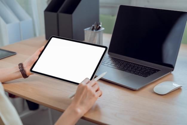 女性の手は、空白のコピースペース画面でタブレットとデジタルペンを保持します。オフィスのテーブルの上のノートパソコン。