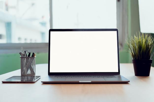 ラップトップおよびタブレットの空白コピースペース画面。オフィスのテーブルの上。