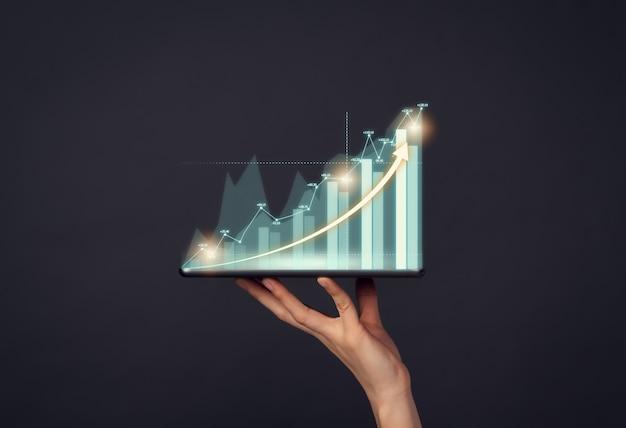 コンセプト株式市場取引所。デジタルタブレットを押しながら財務グラフを示す手。