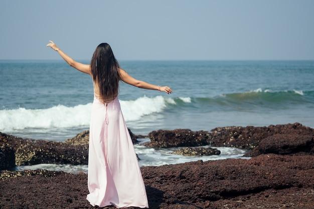 Женщина смотрит на море со спины