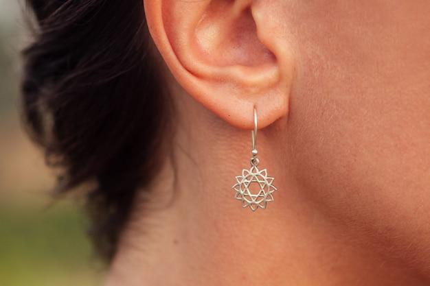 耳に暗いイヤリングを持つ素敵な女性