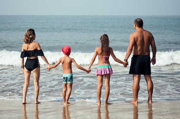 Сильная семья гуляет по пляжу со спины