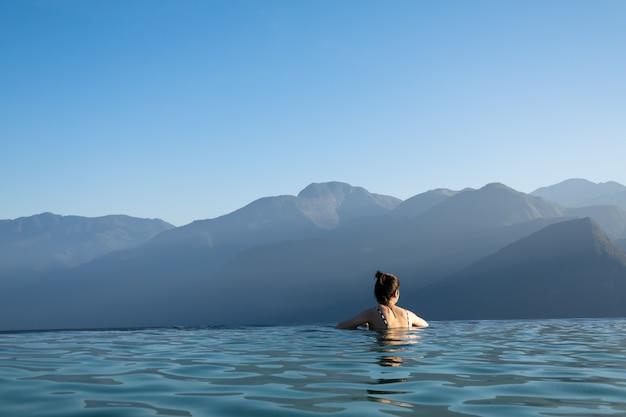 Сексуальная женщина расслабляющий в пейзажном бассейне, глядя на потрясающий вид на горы на роскошный курорт / концепция отдыха