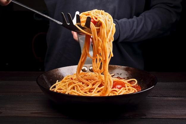 Мужчина готовит спагетти макароны с помидорами и специями.