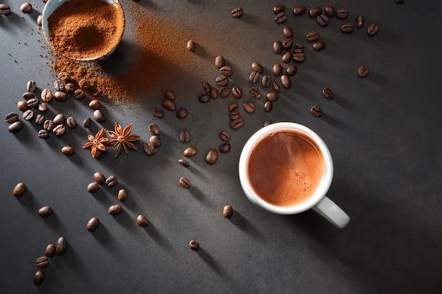 Кофе в чашку белого и кофейных зерен на столе.