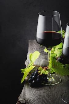 Стакан красного вина заделывают на старый деревянный стол