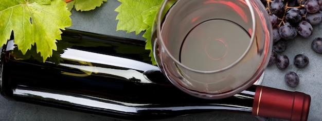 Стакан красного вина, бутылка и виноград на столе.