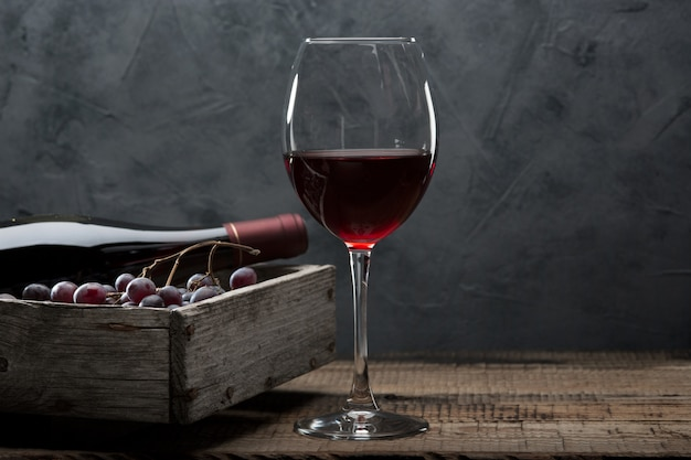 Бутылка вина, бокал, гроздь винограда и виноградные листья на старый деревянный стол.